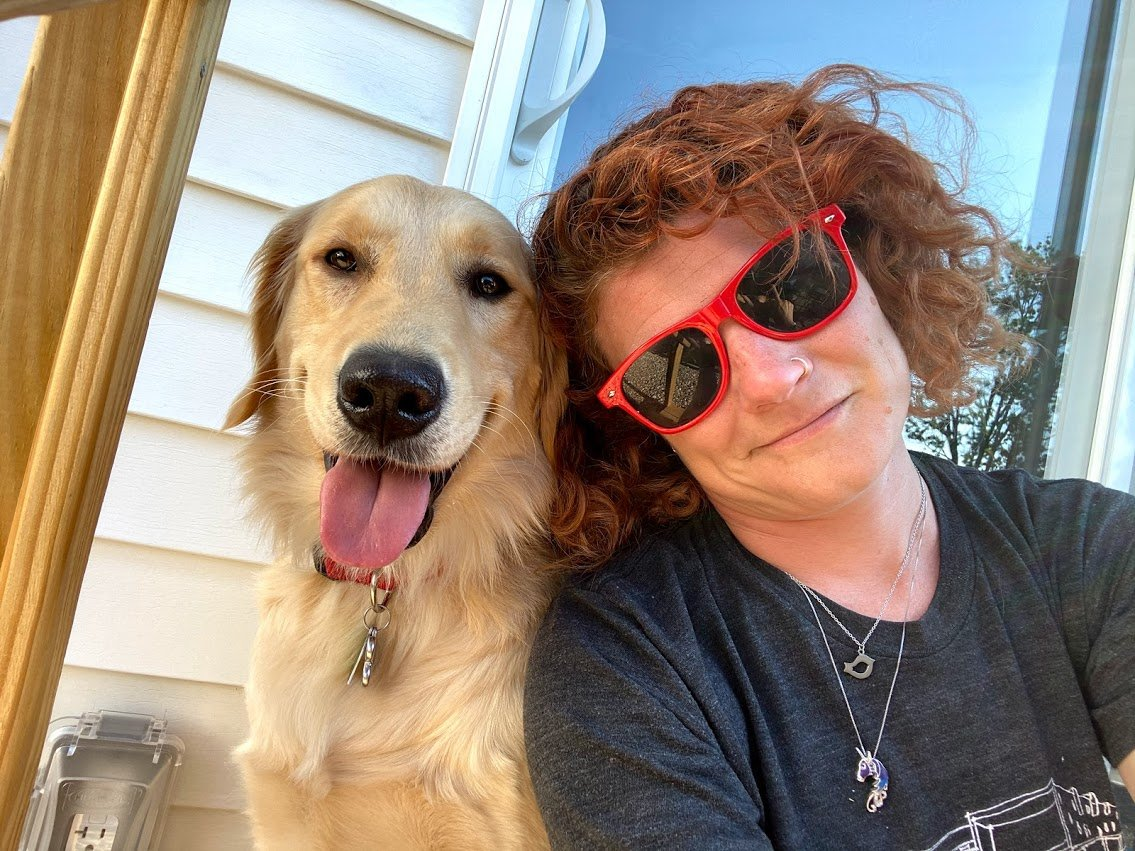 Golden retriever facing the camera sitting next to caucasian woman with reddish brown hair in a black t-shirt wearing red sunglasses and smiling
